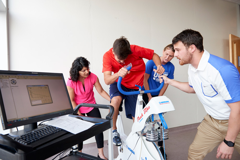Researchers testing and measuring vital statistics of a cyclist
